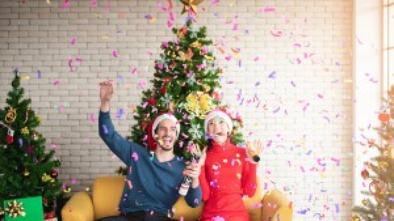 man-and-woman-wearing-santa-hats-sitting-on-sofa-popping-a-3183392-300x200